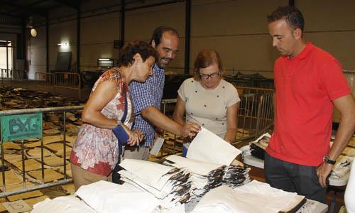 El archivero municipal, Julio Mayo, con otros técnicos analizando los restos quemados. Foto del Correo de Andalucía