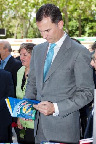 El Príncipe Felipe hojea un libro infantil de Ediciones SM durante su visita a la caseta de SM. ©SM/Sergio Cuesta